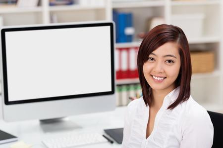 Atraktivní mladá asijské podnikatelka pomocí stolního počítače sedí v přední části polotovaru monitoru obrátil se usmívat do kamery