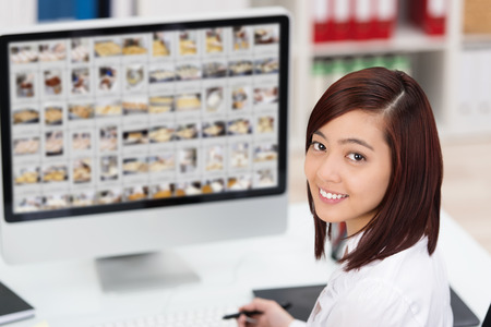 Young Asian woman editing photographs on a large desktop monitor turning to smile at the camera
