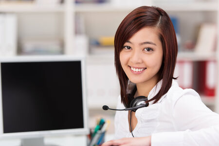front office: Smiling young Asian woman with a headset around her neck sitting at her desk in the office in front of a desktop computer taking a break from her call centre or reception duties to smile at the camera Stock Photo