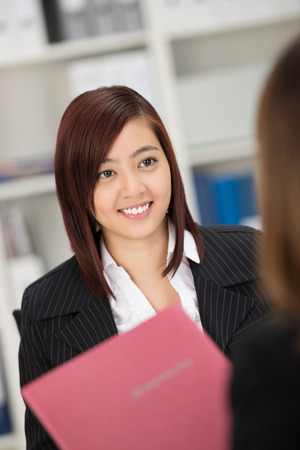 Beautiful young stylish Asian woman being interviewed for a job sitting holding her curriculum vitae in her hands photo