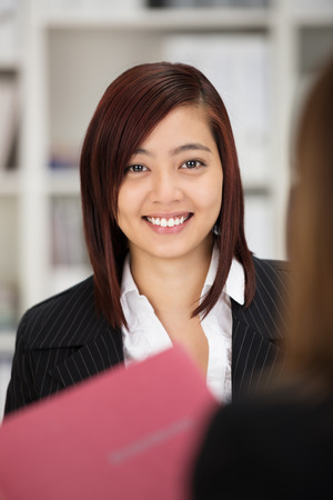 applicant: Happy successful young female Asian job applicant in a stylish jacket looking at the camera with a smile as she clutches her curriculum vita Stock Photo