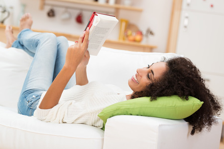 couch: Beautiful young African American woman reading a book lying comfortably on her back on a couch in the living room in her jeans