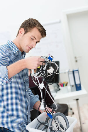 Handsome young businessman holding a tangle of computer cables in his hand above a plastic bin as he converts his office to a wireless environment photo