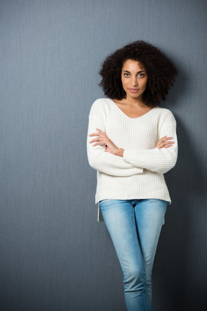 Beautiful serious African American woman leaning against a dark background with crossed legs and folded arms looking at the camera with copyspace and vignetting