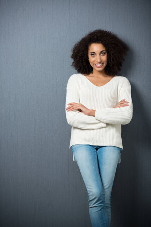 Attractive confident African american woman standing leaning on a dark background with crossed arms giving the camera a beautiful smile photo