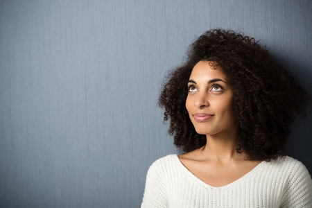 Pretty African American woman with a curly afro hairdo standing daydreaming against a dark background with copyspace as she stares into the air with a smile photo