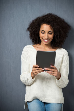 Beautiful young Afro-american woman with a bushy afro hairstyle smiling in pleasure as she reads the screen of her tablet computer on a grey background photo