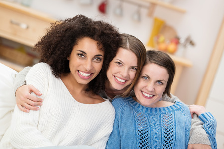 three persons: Happy multiethnic group of beautiful young female friends sitting arm in arm on a sofa in the living room smiling at the camera Stock Photo