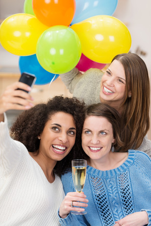 Group of friends celebrating with flutes of champagne taking a self portrait on a mobile phone with a bunch of colorful party balloons as they laugh and joke photo