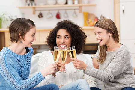 room mate: Three multiethnic attractive young women celebrating at home with champagne toasting each other as they laugh and smile Stock Photo