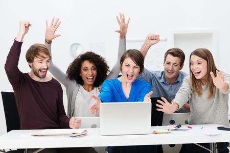 exitacion: Emocionado equipo de negocios exitoso de diversas personas jóvenes multiétnica que se sienta en una mesa en la oficina animando exuberante en la celebración de un resultado exitoso en la computadora portátil