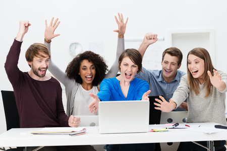 outcome: Excited successful business team of diverse multiethnic young people sitting at a table in the office cheering exuberantly as they celebrate a successful outcome on the laptop computer