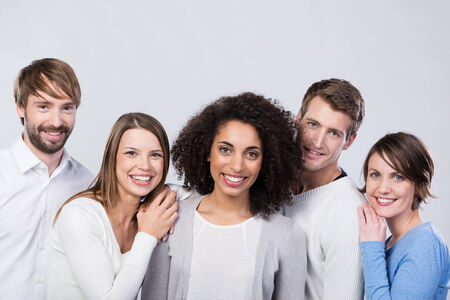 Smiling group of happy young friends posing together grouped around an attractive African American woman photo