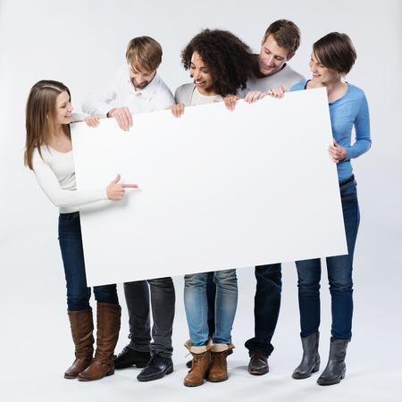 Copyspace には注目を集めて彼女の指でそれを端点で若い女性として保持している空白記号を見てトレンディな冬ファッションで若い友人のグループ