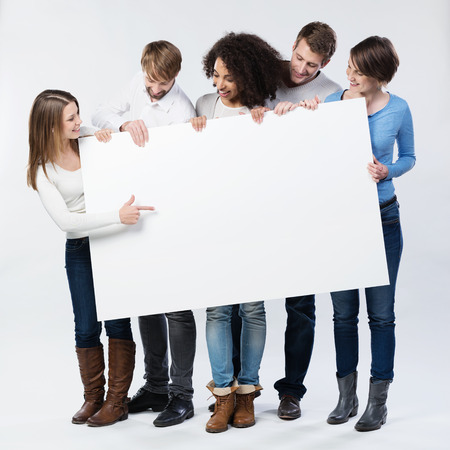 Group of young friends in trendy winter fashion standing looking at a blank sign that they are holding as the young woman on the end points to it with her finger drawing their attention to copyspace 版權商用圖片