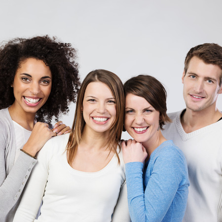 vivacious: Three vivacious beautiful laughing girls with a young male friend posing close together on a grey studio background, upper body portrait