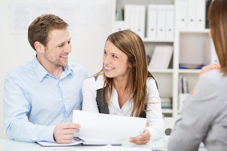 Young couple sitting at a desk in the office of their agent or adviser discussing an investment presentation on a document they are holding photo