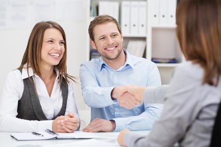 Lachende jongeman handen schudden met een verzekeringsagent of beleggingsadviseur als hij zit in een vergadering met zijn vrouw in haar kantoor Stockfoto