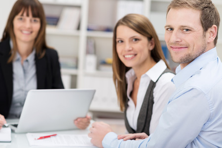 insurer: Attractive smiling couple talking to an agent or investment adviser sitting at a desk in her office turning to smile at the camera Stock Photo