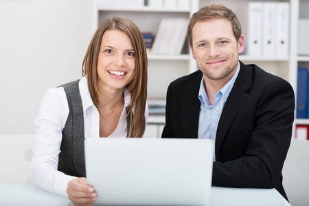 Attractive friendly young businessman and woman sitting at a desk together in the office sharing a laptop as they pool their ideas photo
