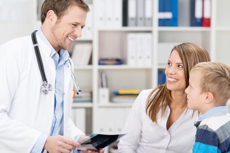 přátelský: Úsměv přátelský hezký rodinný praktický lékař radit s matkou a malé dítě v jeho ordinaci drží x-ray v ruce