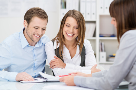 happy client: Investment adviser giving a presentation to a friendly smiling young couple seated at her desk in the office Stock Photo