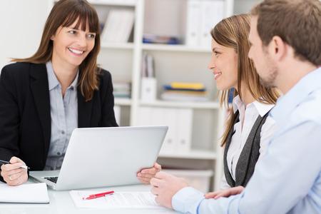 Jong koppel zitten in een kantoor praten met een vrouw makelaar of beleggingsadviseur Stockfoto