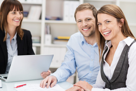 Happy confident young couple in a meeting sitting discussing a presentation and paperwork with their female adviser Stock Photo