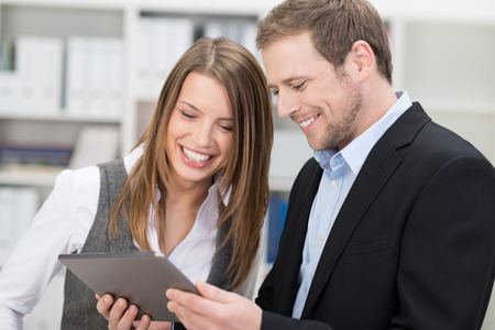 Two attractive stylish young co-workers smiling at information on a tablet held by the man as they stand together in the office photo