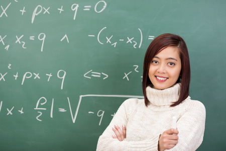 asian teacher: Confident beautiful young Asian teacher or student standing in front of a blackboard covered in mathematical equations smiling at the camera Stock Photo