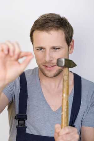 focuses: Handyman about to hammer in a nail holding the hammer at the ready as he focuses on his fingers holding the nail