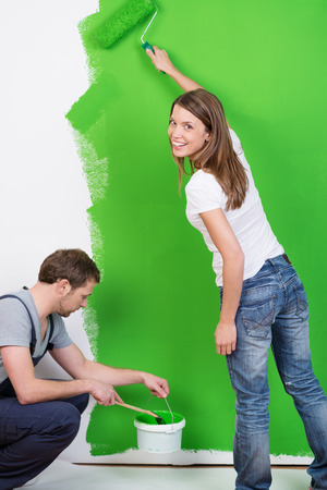 Young couple painting their new home green working as a team as the husband does the skirting boards and the happy young wife smiles at the camera as she uses a roller on the wall Stock Photo