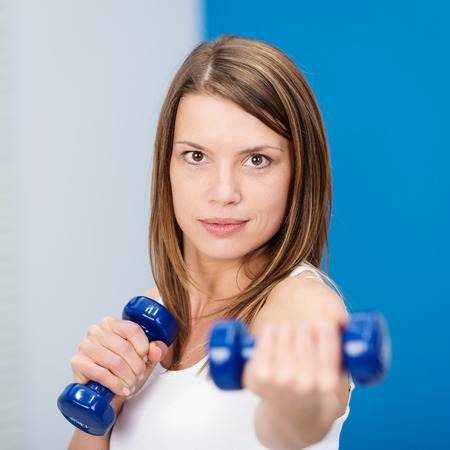 Determined young woman lifting weights working out in a gym with a set of dumbbells to tone and strengthen her muscles,focus to her face