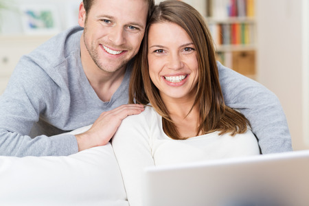Smiling young couple sharing a laptop computer as they sit on a couch at home surfing the internet together and looking up to smile at the camera photo
