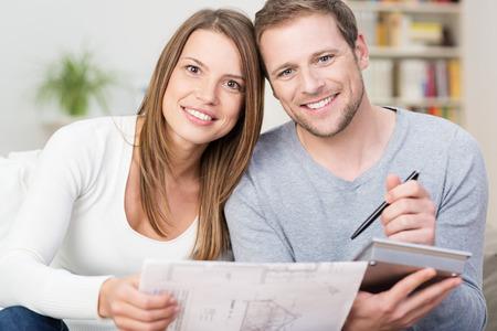 planificacion familiar: Feliz pareja de jóvenes mirando un diagrama de un nuevo producto, junto con una calculadora para ver si pueden permitírselo o si sería adecuado para su casa