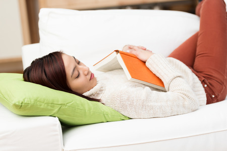 Tired young woman fallen asleep while reading lying on her back on a comfortable couch with her book lying on her chest photo