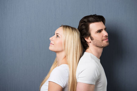 back shots: Attractive young couple standing back to back both staring thoughtfully into the distance with quiet smiles, on grey