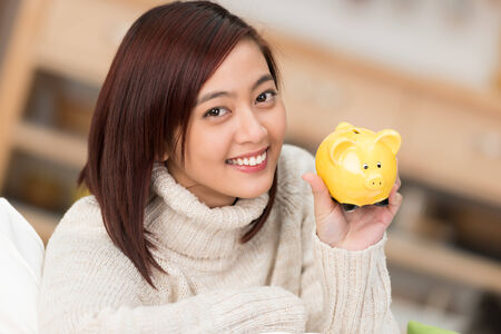 advocates: Smiling young Asian woman holding up a cute little yellow piggy bank as she advocates saving for personal goals and retirement