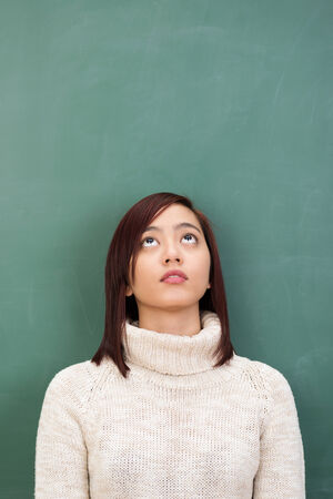 seeking an answer: Young Asian student seeking inspiration standing against a clean blackboard in the classroom looking up towards blank copyspace with imploring eyes as she seeks an answer or solution