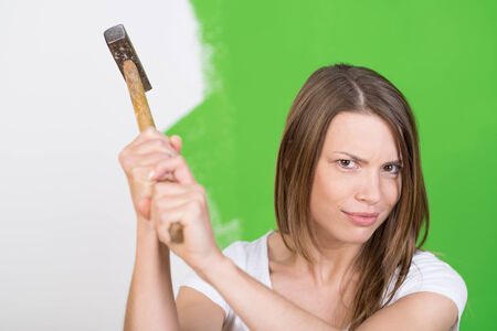 frowns: Angry young woman raising a hammer in the air striking a threatening pose as she frowns frowns at the camera Stock Photo