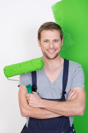 Happy handsome man in dungarees painting his house standing smiling at the camera with his paint roller his folded arms in front of a half finished green wall photo