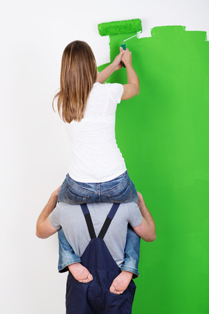 reforming: Improvising when you do not have a ladder as a young woman sits on her husbands shoulders to gain extra height when painting the wall at their home