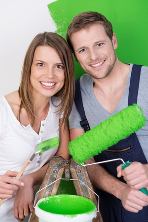 redecorating: Attractive friendly young couple redecorating the house standing on either side of a stepladder holding a paint roller and brush and a tub of green paint