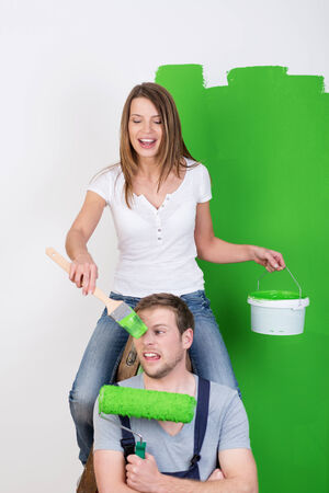 bending over: Young couple having fun as they paint their house with the wife sitting on her husbands shoulders for height bending over to daub him with bright green paint