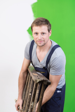 Handsome young painter carrying a wooden stepladder under his arm as he redecorates and paints a house bright green photo