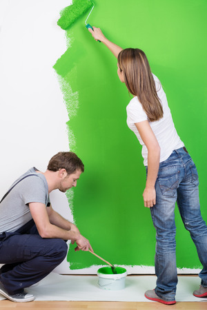 reforming: Young couple redecorating their new home busy painting the walls a modern shade of bright green