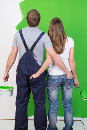 View from behind of a loving young couple admiring the newly painted green wall standing arm in arm holding the paint tub and roller photo
