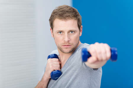 man working out: Determined young man working out with weights at a gym using a pair of dumbbells to strengthen his muscles, focus to his face