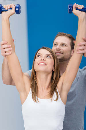 above head: Attractive young woman working out with a personal trainer at a gym lifting a pair of dumbbells above her head as he supports her arms form behind