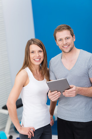 Young couple at the gym monitoring their exercise regime on a tablet computer standing together smiling at the camera
